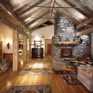 Rustik inredning av ett vardagsrum, med mellanmörkt trägolv, en standard öppen spis och en spiselkrans i sten