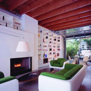 Diseño de biblioteca en casa moderna con suelo de cemento y chimenea tradicional