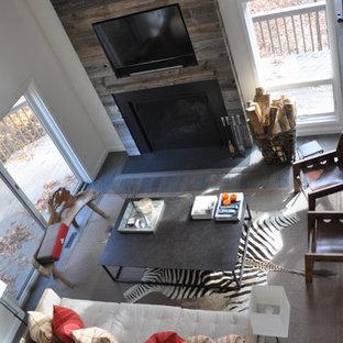 Foto di un soggiorno industriale di medie dimensioni e aperto con pareti bianche, parquet scuro, camino classico, cornice del camino in legno e TV a parete