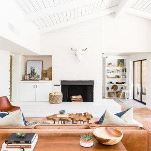 Idéer för amerikanska vardagsrum, med vita väggar, en standard öppen spis, en spiselkrans i tegelsten och orange golv