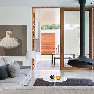 Foto de salón para visitas moderno con paredes blancas y chimeneas suspendidas