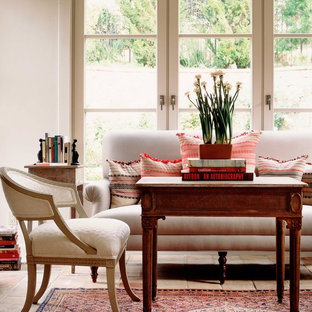 Design ideas for a traditional living room in Orange County with white walls and brick floors.