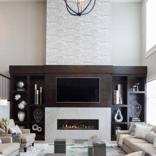 カルガリーの巨大なコンテンポラリースタイルのおしゃれなLDK (フォーマル、ベージュの壁、淡色無垢フローリング、標準型暖炉、石材の暖炉まわり、壁掛け型テレビ、グレーの床) の写真