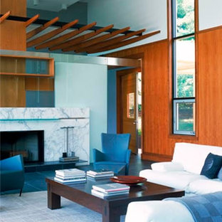 Foto de salón para visitas abierto, actual, grande, sin televisor, con paredes marrones, suelo de pizarra, chimenea tradicional, marco de chimenea de piedra y suelo azul