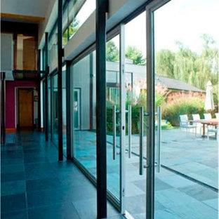 Imagen de salón para visitas abierto, actual, grande, sin televisor, con paredes marrones, suelo de pizarra, chimenea tradicional, marco de chimenea de piedra y suelo azul