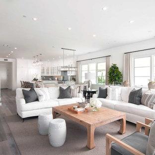 Exemple d'un salon bord de mer ouvert avec un mur blanc, un sol en bois foncé, une cheminée standard et un sol gris.