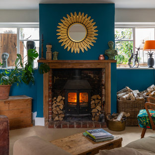 Inspiration for an eclectic living room in London with blue walls, a wood burning stove, no tv and beige floors.