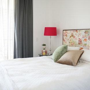 Immagine di un piccolo soggiorno moderno aperto con sala formale, pareti bianche, pavimento in laminato, nessun camino, TV a parete e pavimento marrone