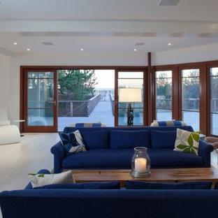 ニューヨークの広いビーチスタイルのおしゃれなLDK (白い壁、淡色無垢フローリング、標準型暖炉、石材の暖炉まわり、テレビなし、白い床) の写真