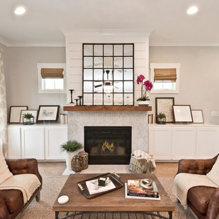 Photo of a country living room in Atlanta with grey walls, medium hardwood floors, a standard fireplace, a stone fireplace surround and white floor.