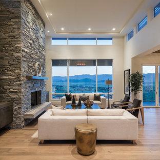 Modelo de salón para visitas abierto, contemporáneo, grande, sin televisor, con suelo de madera en tonos medios, chimenea tradicional, marco de chimenea de piedra y paredes blancas