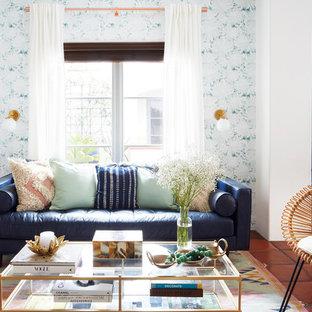 Aménagement d'un petit salon rétro ouvert avec un sol en carreau de terre cuite, une salle de réception, un mur multicolore et un sol rouge.