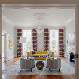 Foto di un grande soggiorno minimal aperto con sala formale, pareti grigie, pavimento in legno massello medio, camino classico, cornice del camino in pietra e nessuna TV