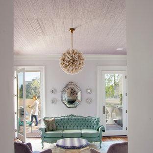Imagen de salón para visitas actual, de tamaño medio, sin televisor, con paredes púrpuras y suelo de madera en tonos medios