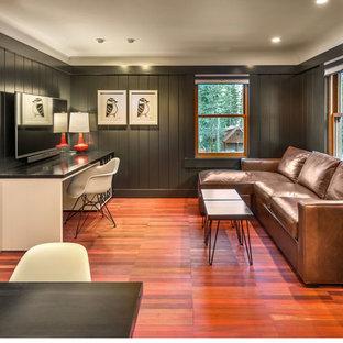 Immagine di un piccolo soggiorno tradizionale aperto con pareti nere, pavimento in legno massello medio, nessun camino e TV a parete