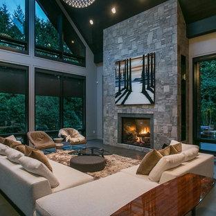 Foto di un grande soggiorno minimalista aperto con pareti grigie, pavimento in ardesia, camino classico, cornice del camino in pietra e nessuna TV