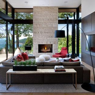 Diseño de salón abierto, moderno, grande, con pared multimedia, suelo beige, suelo de madera en tonos medios, chimenea tradicional y marco de chimenea de piedra
