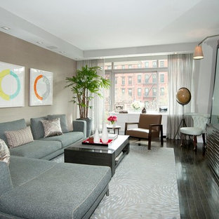 Example of a large trendy open concept dark wood floor living room design in New York with beige walls and a wall-mounted tv