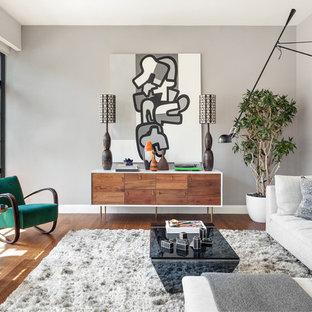 Ejemplo de salón abierto, contemporáneo, grande, sin chimenea, con paredes grises y suelo de madera en tonos medios