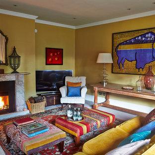 Foto de salón cerrado, ecléctico, grande, con paredes amarillas, moqueta, chimenea tradicional, marco de chimenea de piedra y televisor independiente