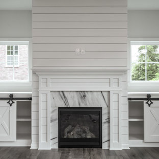 Example of a classic open concept medium tone wood floor, brown floor and shiplap wall living room design in Louisville with white walls, a standard fireplace and a shiplap fireplace