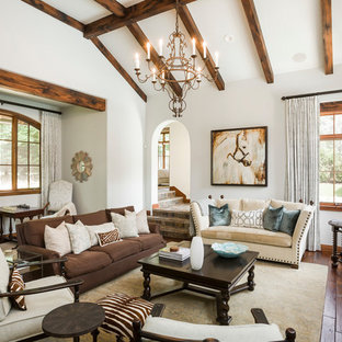 Large tuscan dark wood floor and brown floor living room photo in Austin with white walls, a standard fireplace and a wall-mounted tv