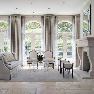 Großes, Repräsentatives, Offenes, Fernseherloses Wohnzimmer mit beiger Wandfarbe, Kamin, Keramikboden und Kaminumrandung aus Stein in Los Angeles