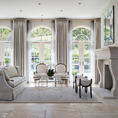 Example of a large french country formal and open concept ceramic tile living room design in Los Angeles with beige walls, a standard fireplace, a stone fireplace and no tv