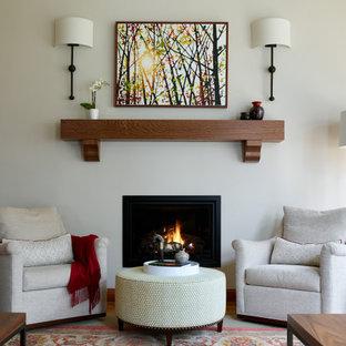 Klassisk inredning av ett mycket stort allrum med öppen planlösning, med grå väggar, mellanmörkt trägolv, en standard öppen spis, en spiselkrans i metall, en inbyggd mediavägg och brunt golv
