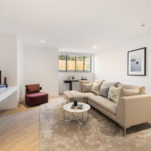 Inspiration for a contemporary living room in London with white walls, light hardwood flooring and a wall mounted tv.