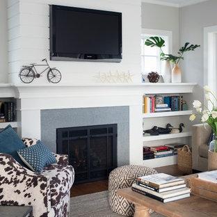 ニューヨークの中サイズのビーチスタイルのおしゃれな独立型リビング (フォーマル、グレーの壁、横長型暖炉、コンクリートの暖炉まわり、壁掛け型テレビ、濃色無垢フローリング、茶色い床) の写真