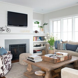 Example of a mid-sized coastal open concept medium tone wood floor and brown floor living room library design in New York with gray walls, a standard fireplace, a wall-mounted tv and a concrete fireplace