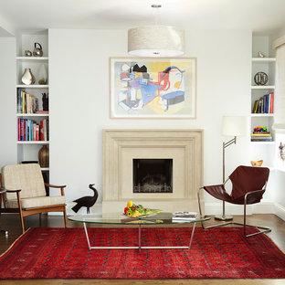 Esempio di un soggiorno chic di medie dimensioni con pareti bianche, pavimento in legno massello medio, camino classico, nessuna TV e cornice del camino in cemento