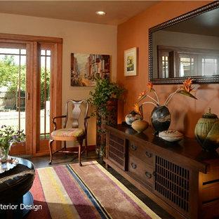 サンフランシスコの中サイズのエクレクティックスタイルのおしゃれな独立型リビング (フォーマル、オレンジの壁、コンクリートの床、茶色い床) の写真