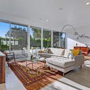 ロサンゼルスのミッドセンチュリースタイルのおしゃれなリビング (白い壁、コンクリートの床) の写真