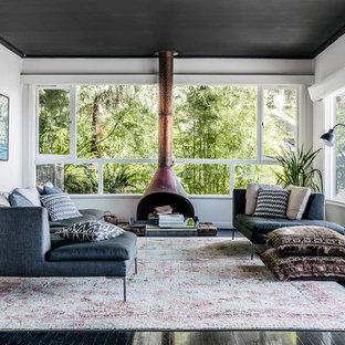 Diseño de salón contemporáneo con paredes blancas, suelo de madera pintada, estufa de leña y suelo negro