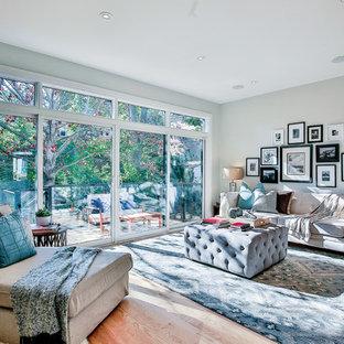 Ejemplo de salón abierto, clásico renovado, de tamaño medio, sin televisor, con paredes grises, suelo de madera clara, chimenea tradicional y marco de chimenea de madera