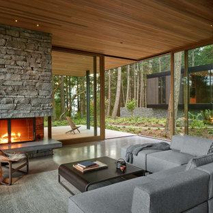 Exemple d'un salon moderne ouvert avec béton au sol, une cheminée standard, un manteau de cheminée en pierre de parement, un sol gris et un plafond en bois.