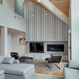 This is an example of a large contemporary open plan living room in Vancouver with grey walls, light hardwood flooring, a standard fireplace and a wall mounted tv.
