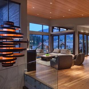 バンクーバーの広いコンテンポラリースタイルのおしゃれなLDK (グレーの壁、無垢フローリング、茶色い床、吊り下げ式暖炉、石材の暖炉まわり、テレビなし) の写真