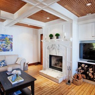 トロントの中サイズのビーチスタイルのおしゃれな独立型リビング (ライブラリー、白い壁、淡色無垢フローリング、標準型暖炉、木材の暖炉まわり、埋込式メディアウォール) の写真