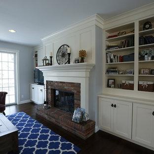 Foto di un soggiorno american style di medie dimensioni e aperto con pareti blu, parquet scuro, camino classico, cornice del camino in mattoni e parete attrezzata