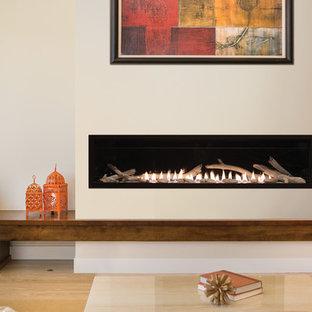 ニューヨークの中サイズの地中海スタイルのおしゃれなLDK (フォーマル、ベージュの壁、淡色無垢フローリング、横長型暖炉、漆喰の暖炉まわり、テレビなし、ベージュの床) の写真