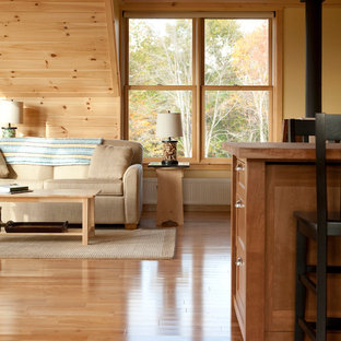 Design ideas for a large country living room in Portland Maine with a library, light hardwood floors and yellow walls.