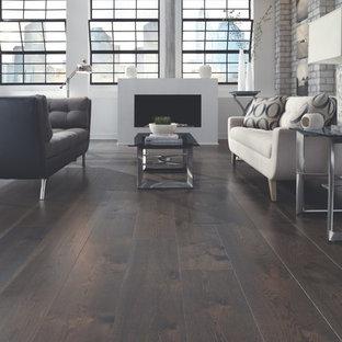 Imagen de salón tipo loft, minimalista, grande, sin televisor, con paredes grises, suelo de madera oscura, chimenea tradicional y marco de chimenea de metal