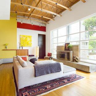 Imagen de salón abierto, actual, sin televisor, con paredes amarillas, suelo de madera en tonos medios, suelo naranja, chimenea tradicional y marco de chimenea de hormigón