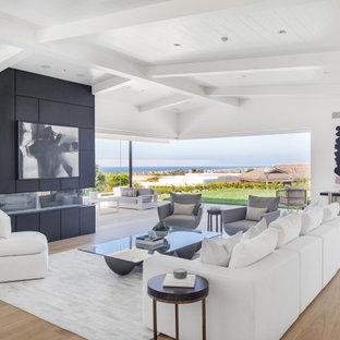 Imagen de salón abierto, retro, con paredes blancas, suelo de madera clara y chimenea lineal
