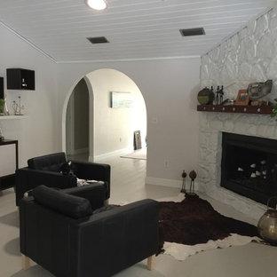 オーランドの中サイズのビーチスタイルのおしゃれな独立型リビング (フォーマル、白い壁、塗装フローリング、コーナー設置型暖炉、石材の暖炉まわり、テレビなし、ベージュの床) の写真