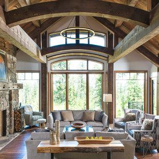 Imagen de salón para visitas rural con paredes blancas, suelo de madera oscura, chimenea tradicional, marco de chimenea de piedra y suelo marrón