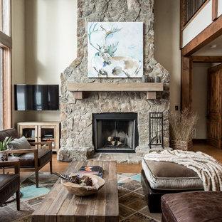 他の地域の大きいラスティックスタイルのおしゃれな独立型リビング (ベージュの壁、無垢フローリング、標準型暖炉、石材の暖炉まわり、壁掛け型テレビ、フォーマル、茶色い床) の写真